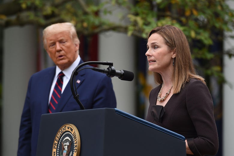 Amy Coney Barrett speaks at a lectern while Trump watches from the side.