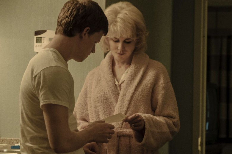Nicole Kidman, in a bathrobe, hands Lucas Hedges a note.