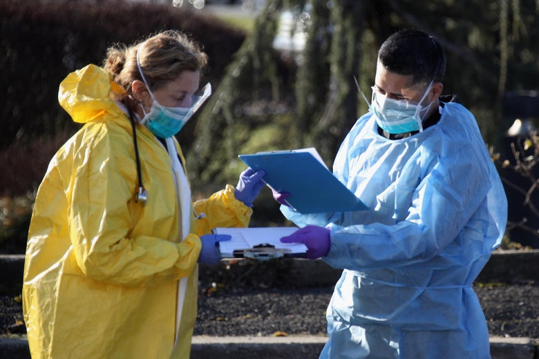A medical worker in a yellow biohazard suit trades charts with a medical worker in a blue biohazard suit.