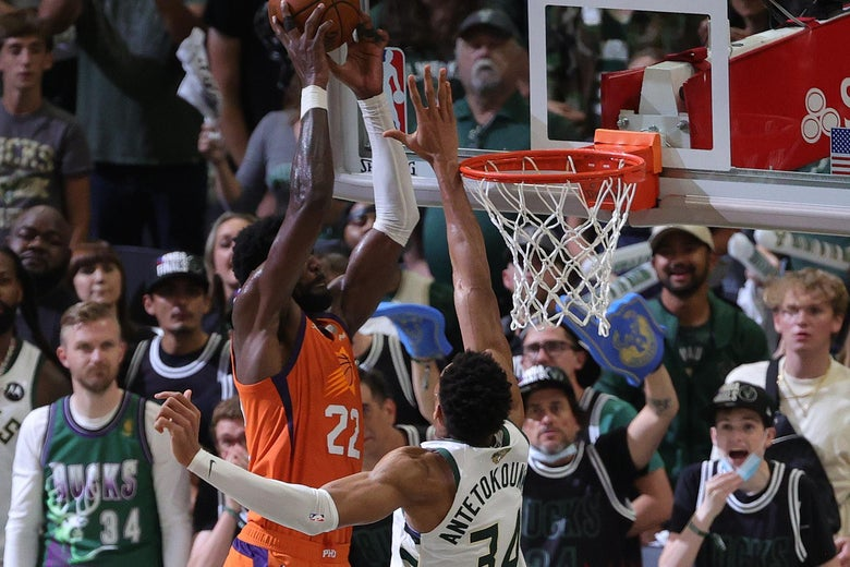 MILWAUKEE, WISCONSIN - JULY 14: Giannis Antetokounmpo #34 of the Milwaukee Bucks defends against Deandre Ayton #22 of the Phoenix Suns during the second half in Game Four of the NBA Finals at Fiserv Forum on July 14, 2021 in Milwaukee, Wisconsin. NOTE TO USER: User expressly acknowledges and agrees that, by downloading and or using this photograph, User is consenting to the terms and conditions of the Getty Images License Agreement.  (Photo by Stacy Revere/Getty Images)