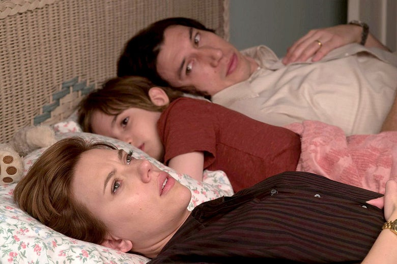 Scarlett Johansson, Azhy Robertson, and Adam Driver lie in bed in this still from Marriage Story.