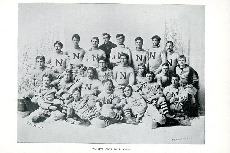 A black-and-white photo of an old-fashioned team of football players posed for the camera.