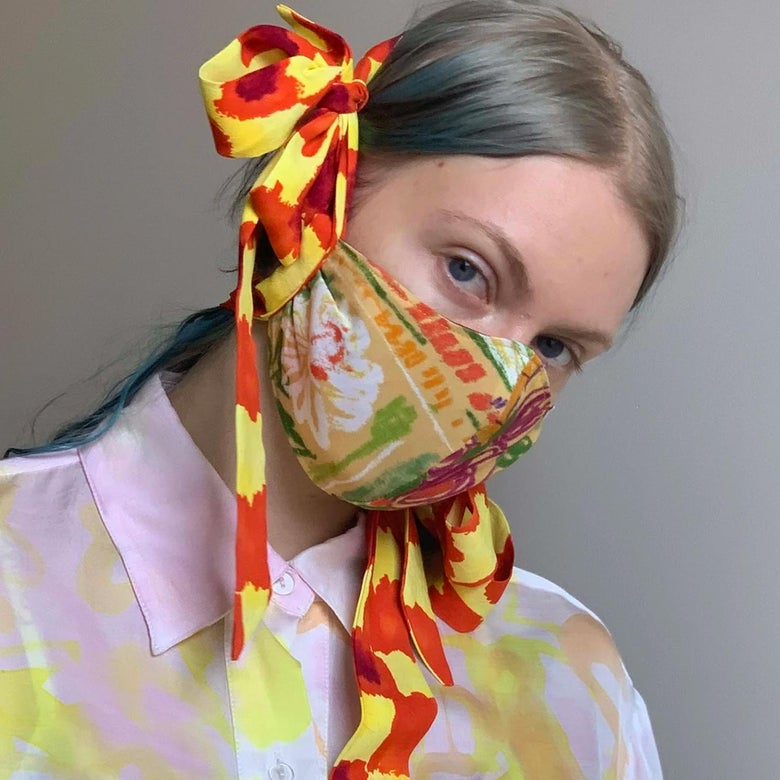 A model with blue hair wears a colorfully patterned face mask with large bows that loop around her head.