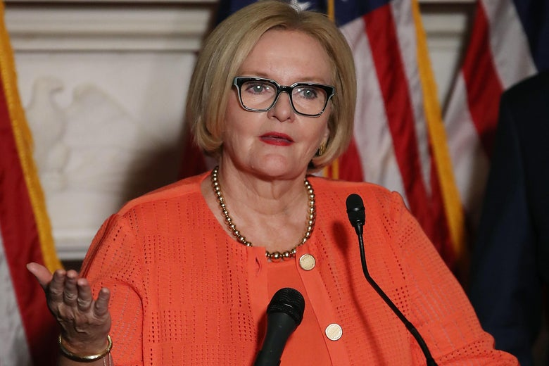 Sen. Claire McCaskill gestures with her right hand while speaking into a microphone during a news conference on Capitol Hill.