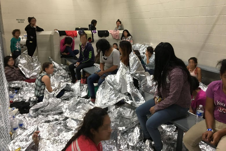 Families crowded inside the detention facility, with aluminum foil blankets strewn about.
