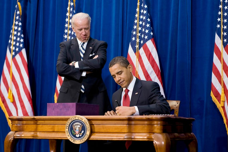 Biden smiles and stands with his arms crossed beside Obama, seated, signing the stimulus bill on a desk, with American flags behind them