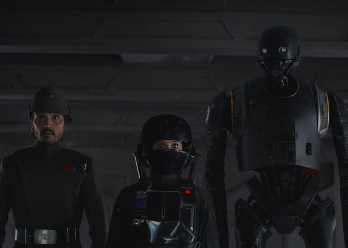 Diego Luna and Felicity Jones wear dark uniforms and walk alongside a tall, gangly robot.
