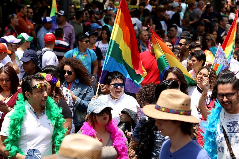 People walk and dance during a Pride parade in Mexico City.