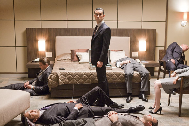 Joseph Gordon Levitt stands in a nice suit amid sleeping people