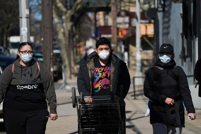 People wear masks while walking in the Borough of Brooklyn on April 4, 2020 in New York.
