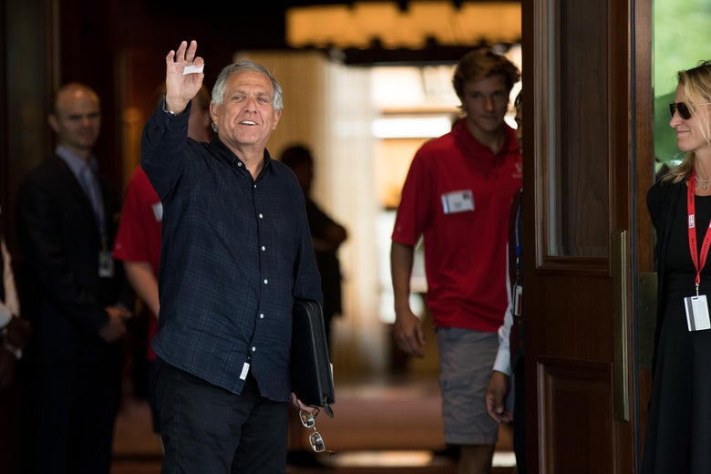 Les Moonves waves as he arrives at a conference.