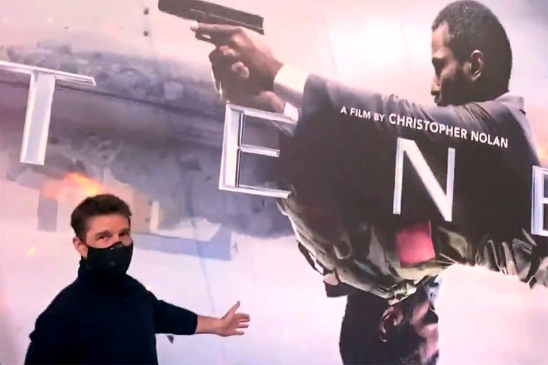 Tom Cruise standing in front a large promotional poster for Tenet.