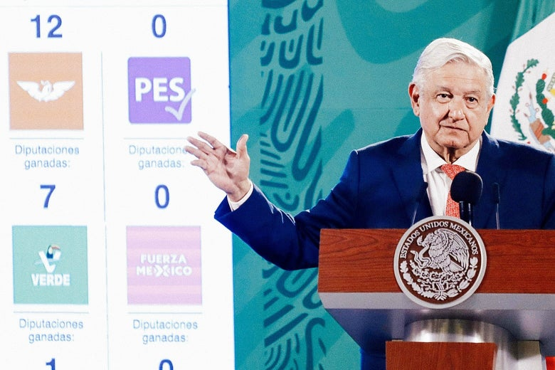 Lopez Obrador stands at a podium gesturing with one arm beside a poster displaying the logos of Mexican political parties, the Green Party among them