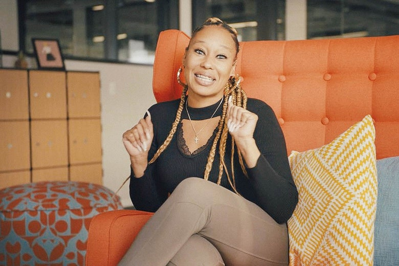 A Black woman with braids clasps holds up her hands as she talks to the camera.
