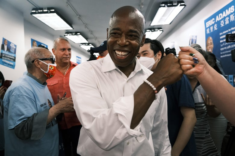 Eric Adams fist-bumps a supporter while standing and smiling in a room.