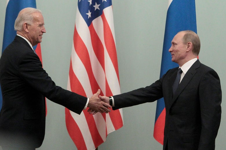 Biden and Putin smile and shake hands in front of American and Russian flags.