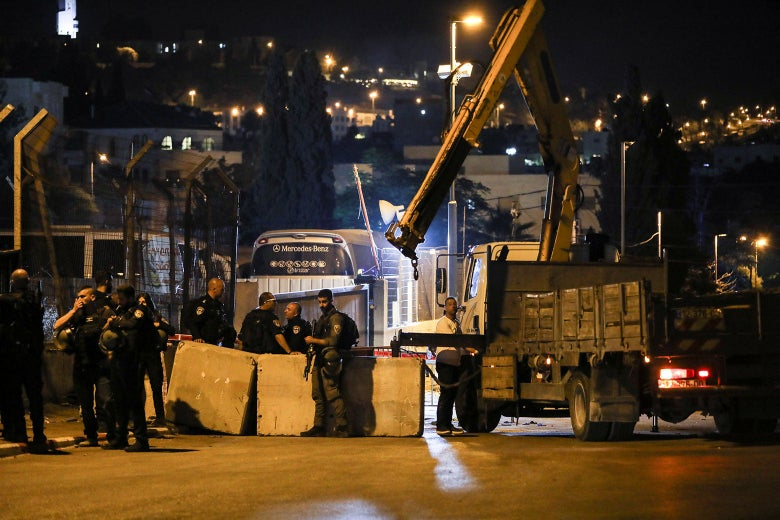 Israeli police stand around street barricades placed by a crane.