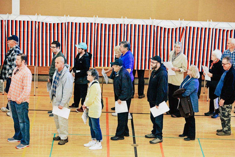 Voters wait in line to cast their votes in a gym, in front of red, white, and blue booths.