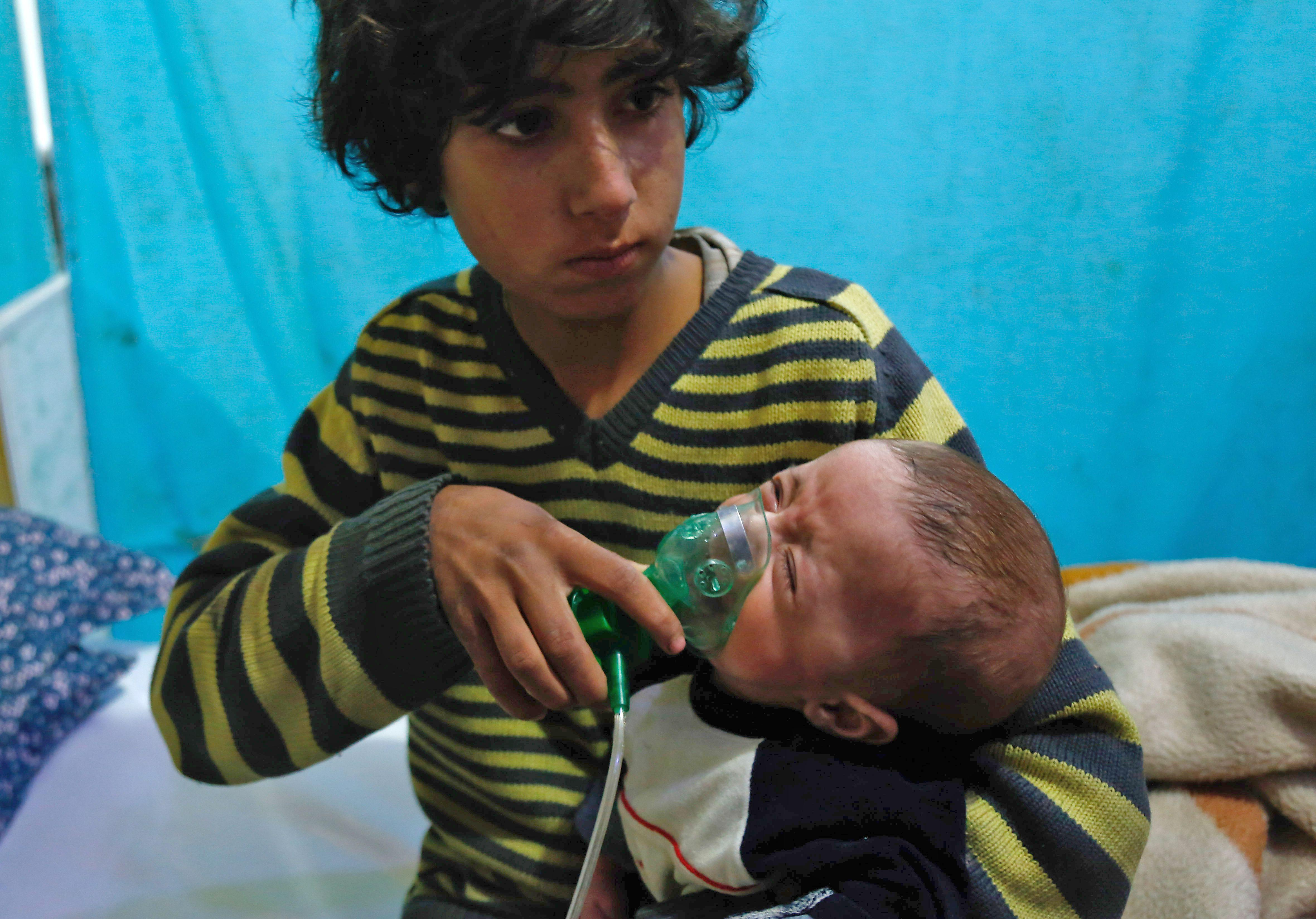 A Syrian boy holds an oxygen mask over the face of an infant.