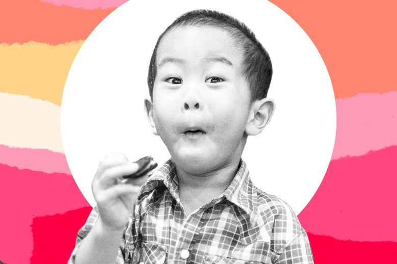 A kid delightedly eating a cookie.