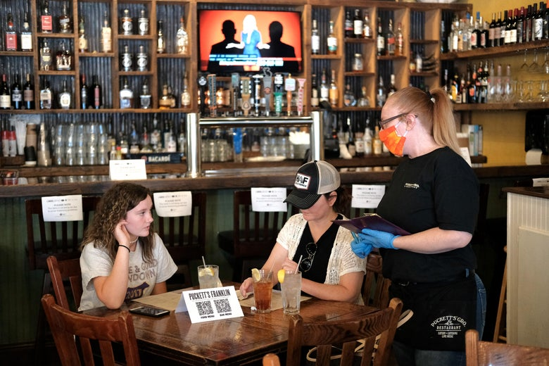 A waitress wearing rubber gloves and a mask taking orders for patrons at Puckett's Grocery & Restaurant on April 27, 2020 in Franklin, Tennessee.