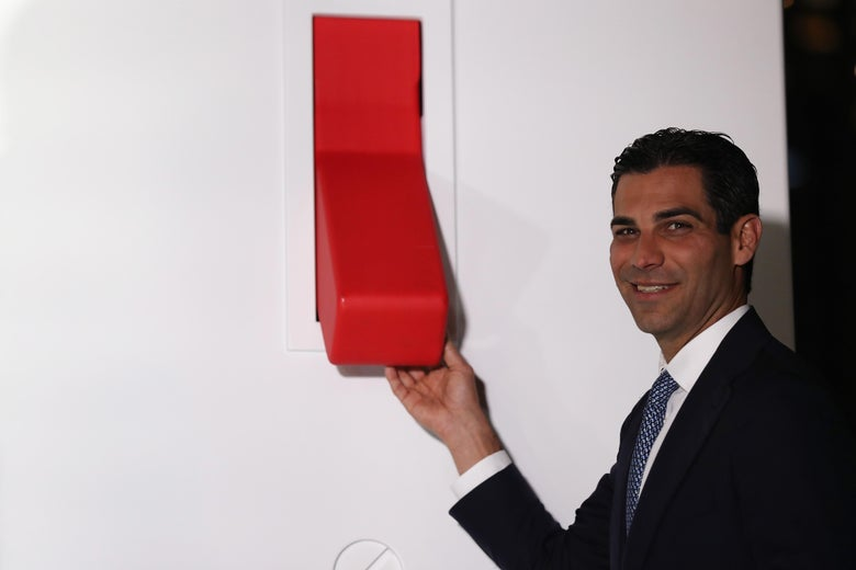 Francis Suarez poses in front of a giant red light switch on a wall at a new development in Miami