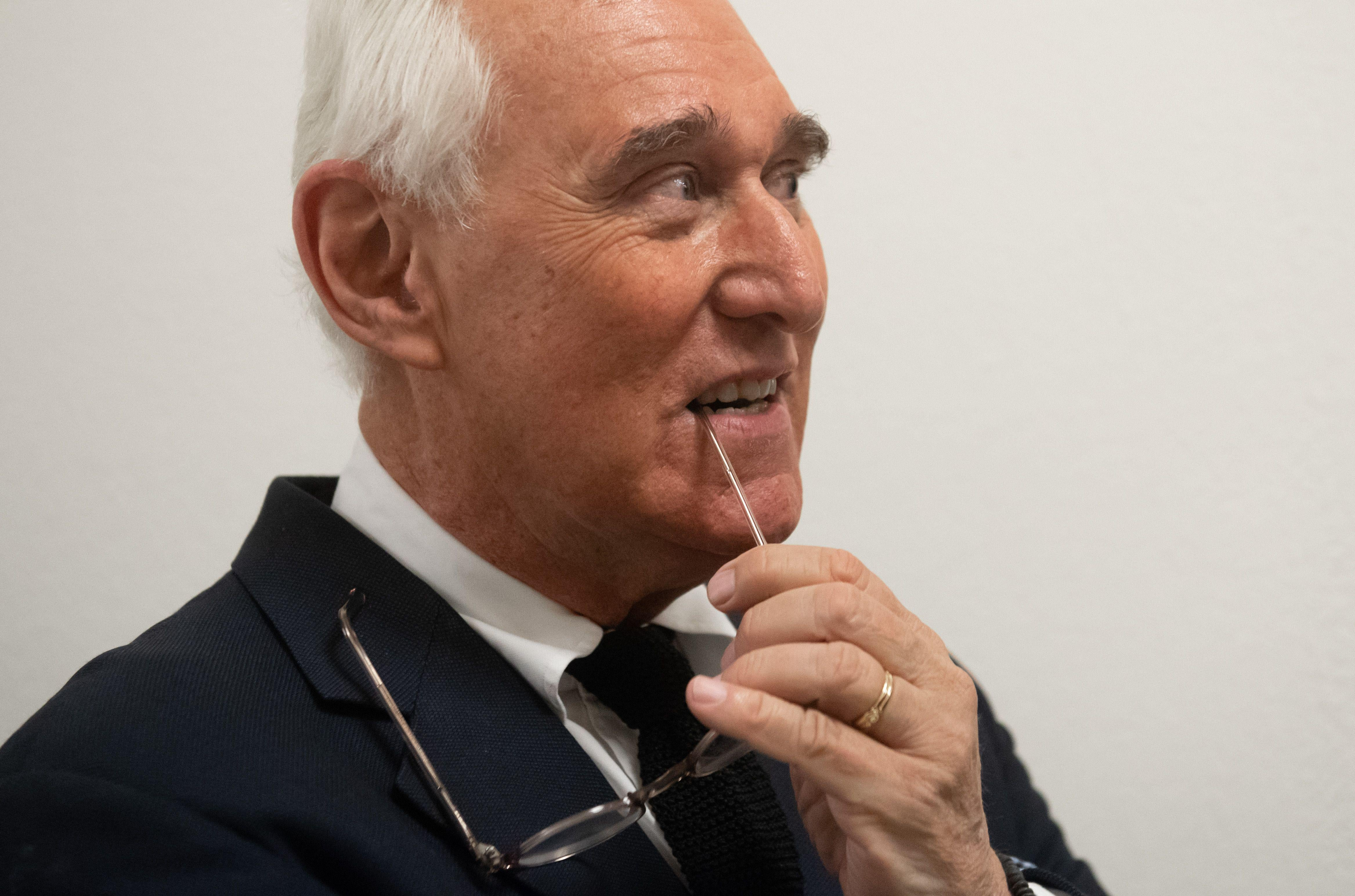Roger Stone with a stem of his glasses in his mouth