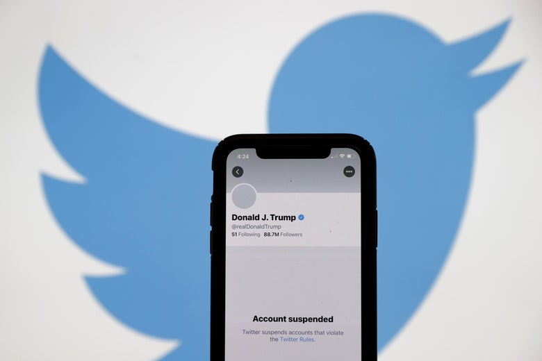 The suspended Twitter account of President Donald Trump on an iPhone screen, with the Twitter bird logo in the background