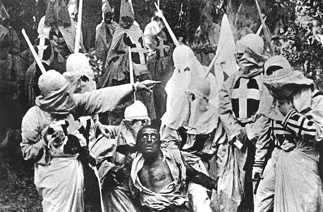 Actors costumed in the full regalia of the Ku Klux Klan chase down a white actor in blackface in a still from The Birth of a Nation.