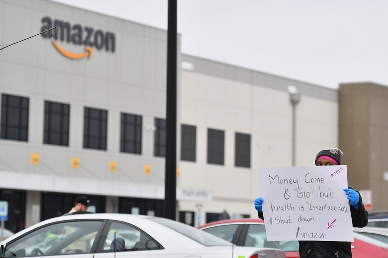 "A protester stands in front of an Amazon facility holding a sign that reads ""Money come and go but health is irreplaceable #Shut down Amazon"""
