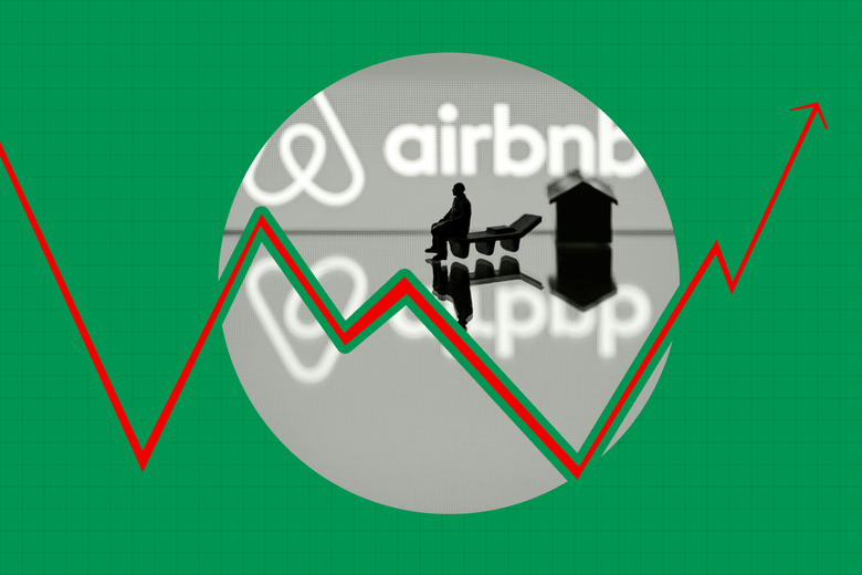 A figurine and a toy house in front of the Airbnb logo