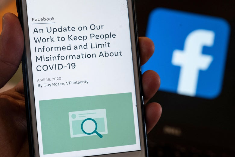 A smart phone screen displays a new policy on Covid-19 misinformation with a Facebook website in the background.