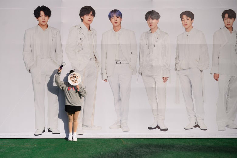 A fan stands in front of a large poster depicting the boy band BTS.