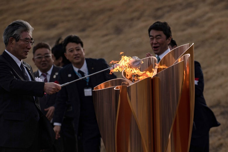 The Tokyo 2020 Olympic flame is displayed being lit by men in suits.