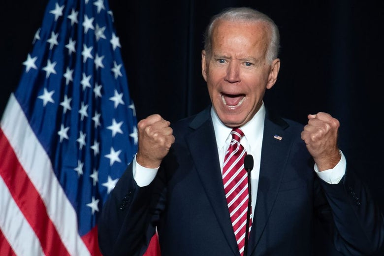 Biden clenches his fists while wearing a suit and tie and standing at a lectern in front of an American flag.