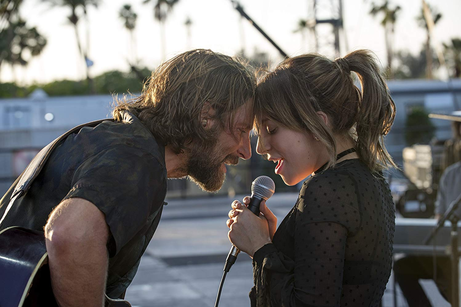 Bradley Cooper, with long, lank hair and a beard, presses his forehead to a brunette Lady Gaga's. He holds a guitar and she holds a microphone.