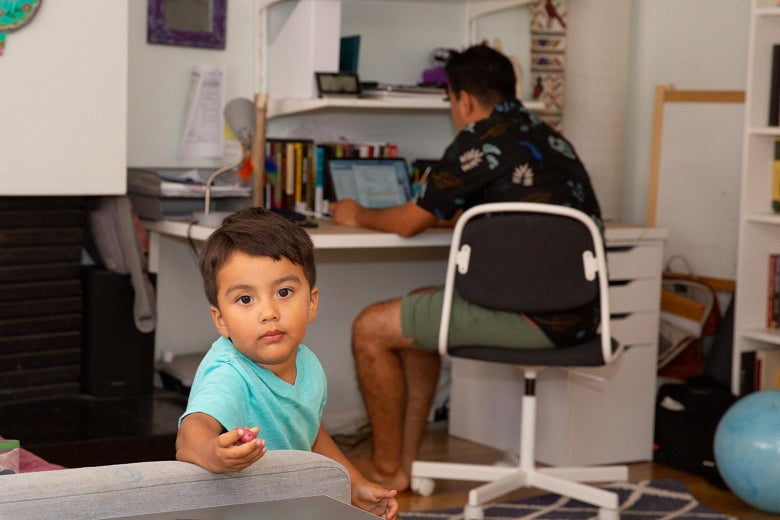 A boy looks toward the camera, reaching forward with a toy in his hand. Behind him, Oscar works on a laptop at a desk.