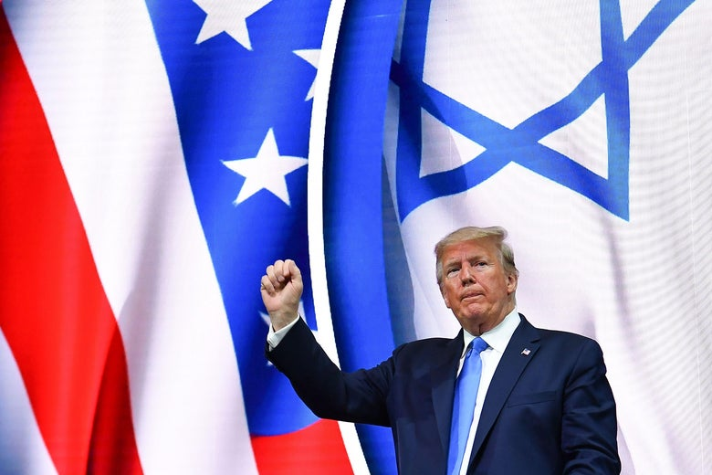 Trump holds up a fist while standing in front of U.S. and Israeli flags.