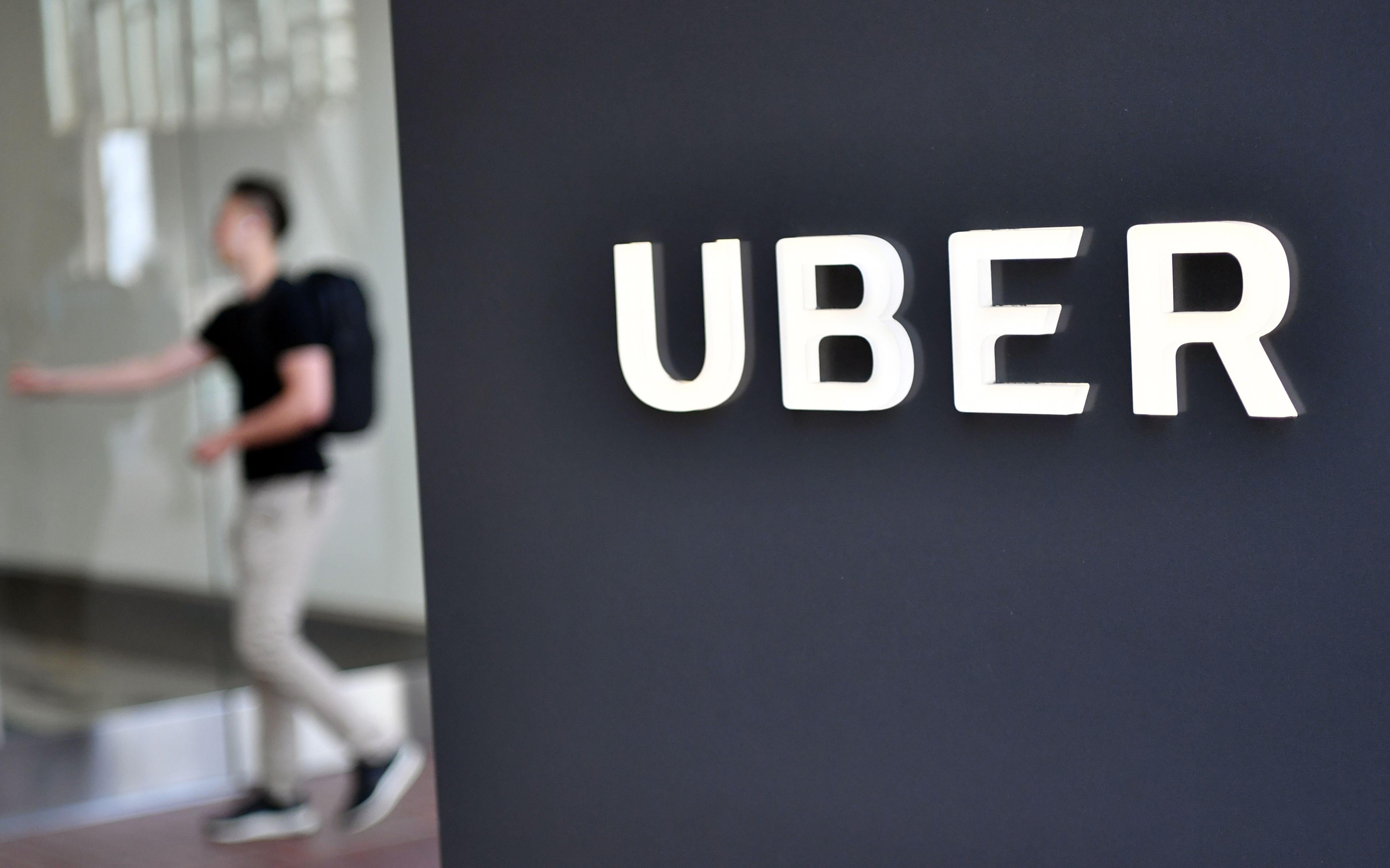 A man walks into the Uber Corporate Headquarters building in San Francisco, California on February 05, 2018.          The billion-dollar trial pitting Alphabet-owned autonomous driving unit Waymo against Uber started in what could be a blockbuster case between two technology giants over alleged theft of trade secrets. The San Francisco courtroom battle will take place as Waymo and Uber race to perfect self-driving cars that people could summon for rides as desired in a turn away from car ownership.          / AFP PHOTO / JOSH EDELSON        (Photo credit should read JOSH EDELSON/AFP/Getty Images)