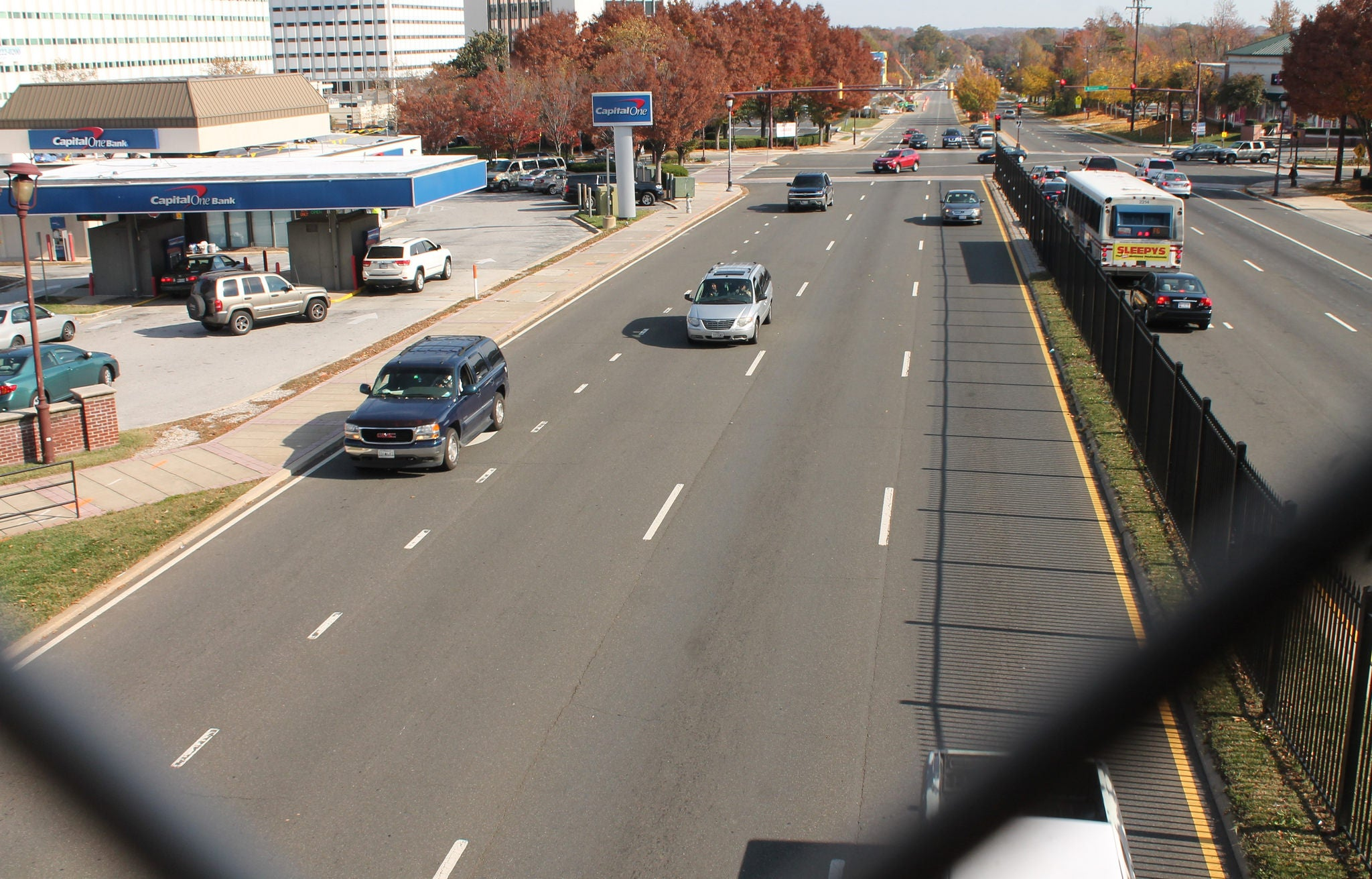 Cars travel on a four-lane road, as seen from an overpass.