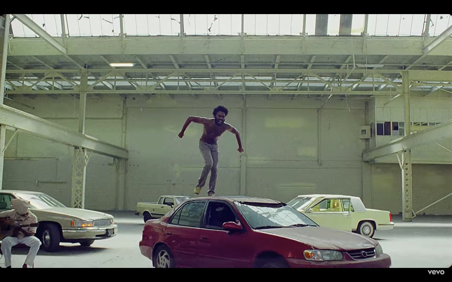 "Childish Gambino (Donald Glover) stands on top of a car in the ""This Is America"" video."