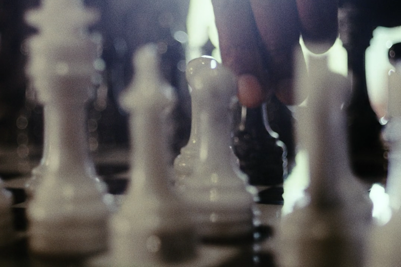 A hand is seen on a pawn in a chessboard.