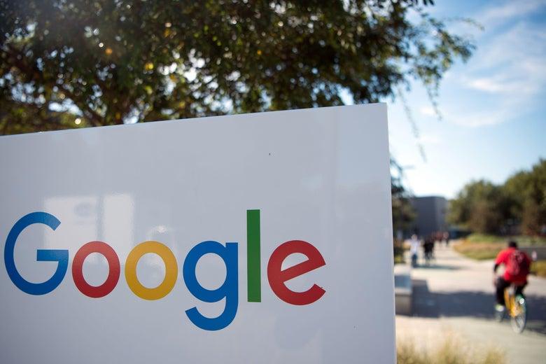 A man rides a bike past a Google sign at the Googleplex in Menlo Park, California.