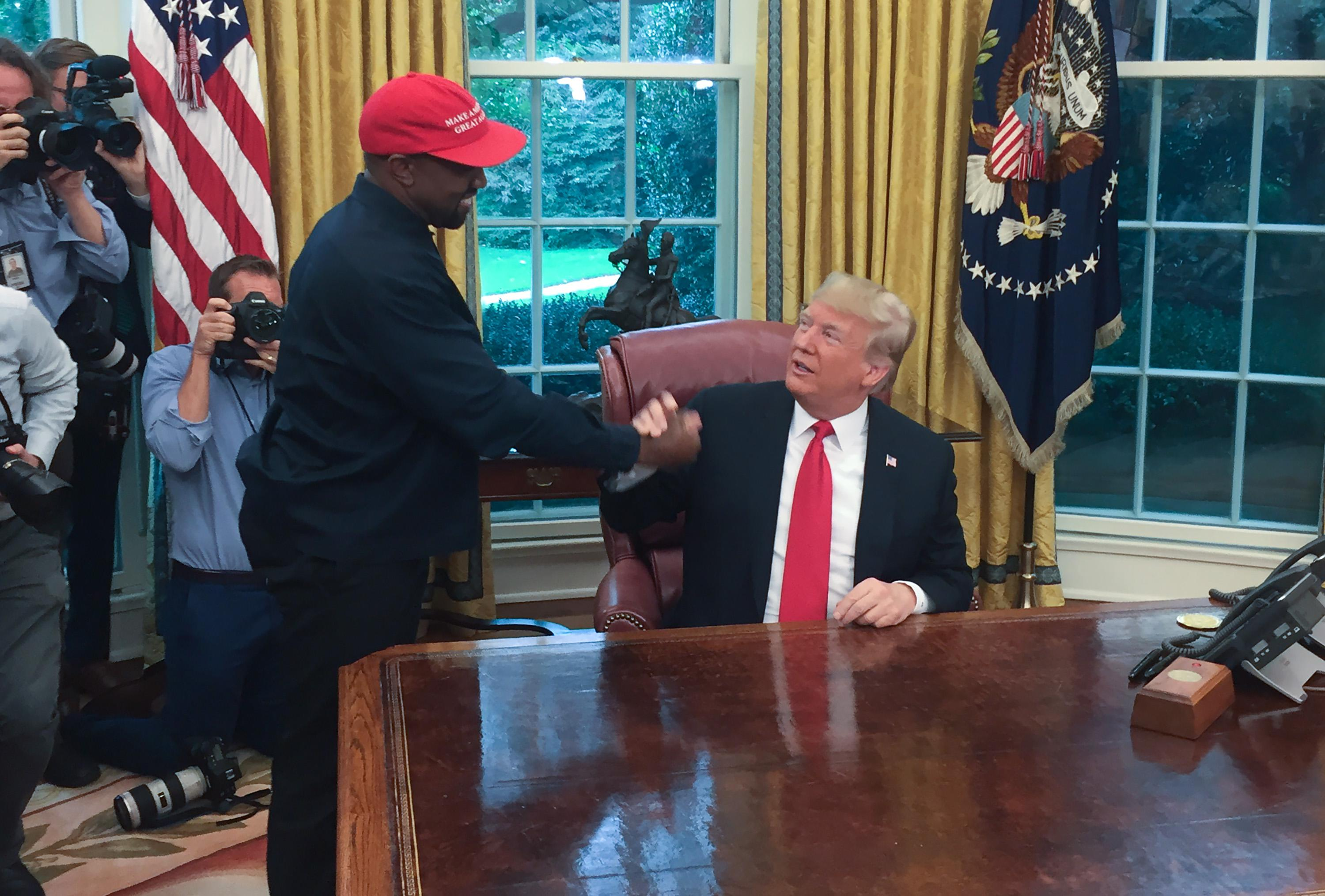 Kanye West, standing and wearing a MAGA hat, shakes hands with Donald Trump, seated at the desk in the Oval Office, as photographers in the background take their picture.