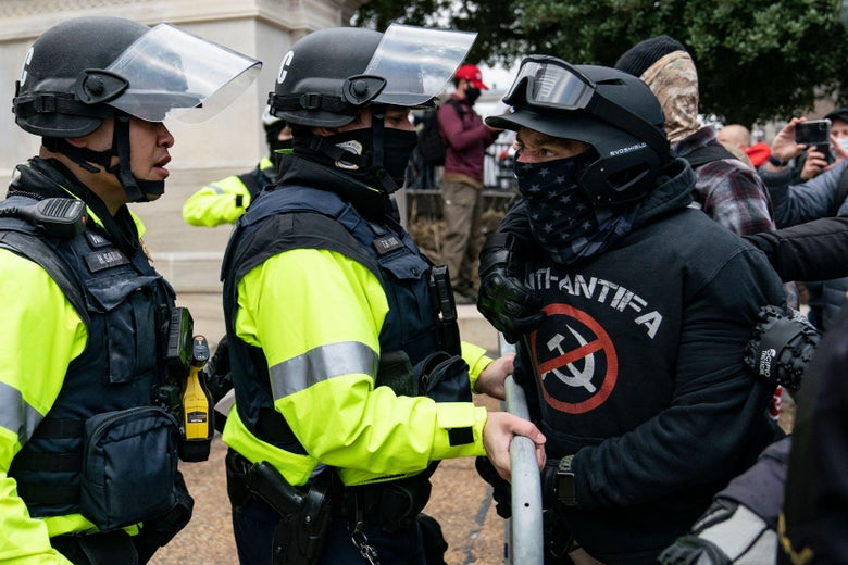 A rioter who claimed to be a member of the Proud Boys, confronts police officers outside the Capitol.