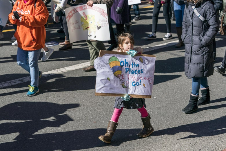 "A young girl holds a Dr. Seuss-inspired sign reading, ""Oh the places I deserve to go."""