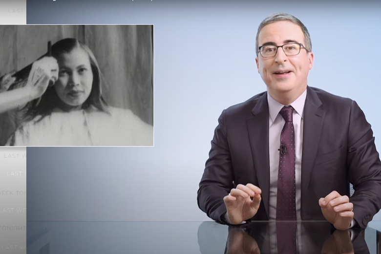 John Oliver sits in his void next to a black-and-white photo of someone running a hot comb through a young Black woman's hair