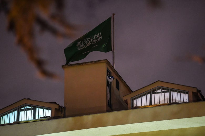 A Turkish investigator stands next to the Saudi flag on the roof of the Saudi consulate at night.
