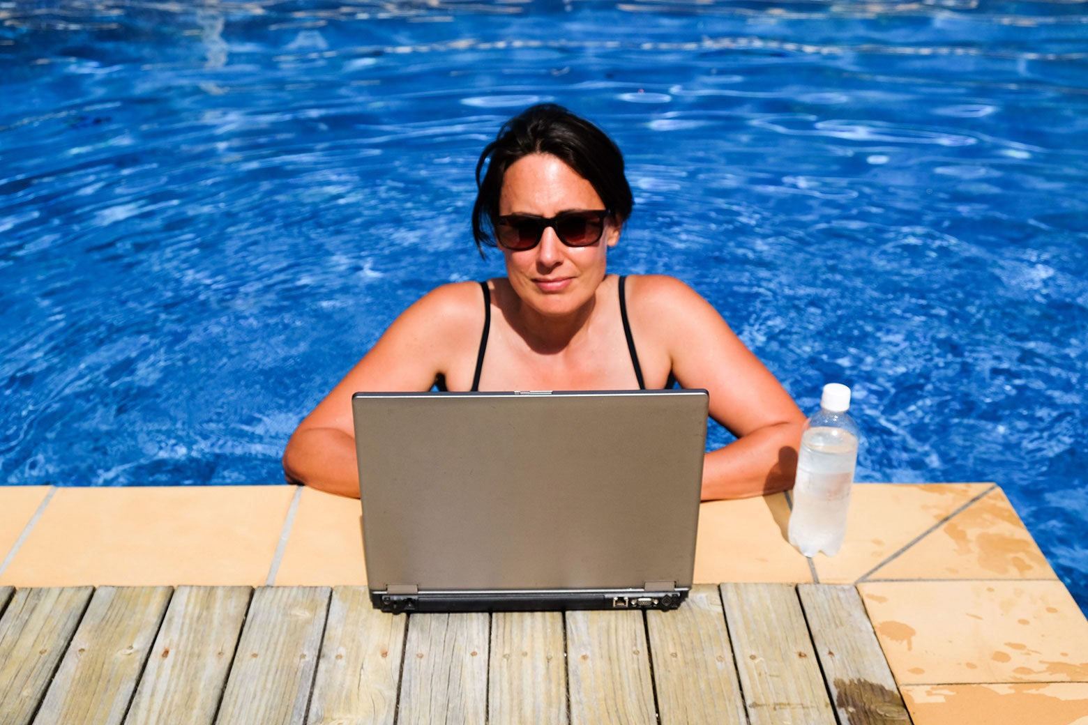A woman in a swimming pool uses a laptop on the deck of the pool.