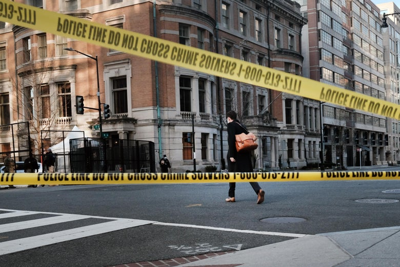 A person crosses an empty street closed off by crime scene tape.